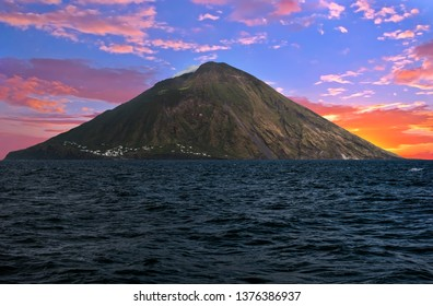 Sunset over Stromboli volcano seen from the boat. Stromboli is one of the eight Aeolian islands and one of three active volcanoes in Italy