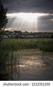sunset over swampland with sunbeams in the distance