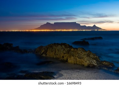 Sunset over Table Mountain with crocodile looking rock in foreground and city skyline