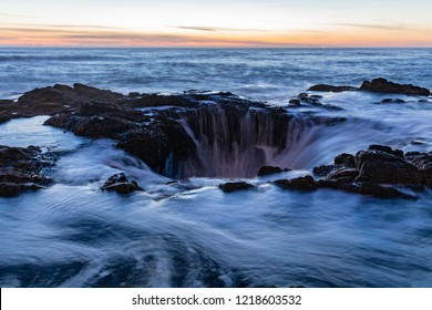Sunset over Thor's Well sunset, a natural sinkhole at Cape Perpetua, Oregon Coast. Long exposure shot of a water draining down the hole at an evening tide