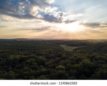 Sunset over the trees with dramatic sky wihh clouds and sunlight. Drone photography above the trees.