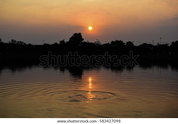 A sunset over trees and lake