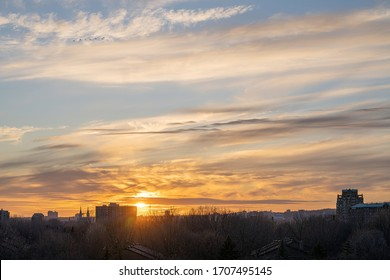 Sunset over Verdun, Quebec, Canada during the golden hour. A church, buildings and trees are silhouetted in the foreground.