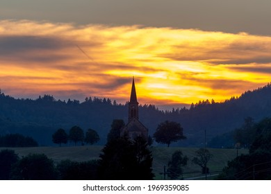 Sunset over the village Hofen in the Black Forest with the silhouette of the church
