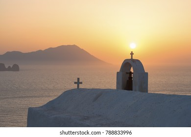 Sunset over a whitewashed church on the island of Milos in Greece with the Aegean Sea in the background.