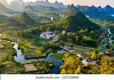 Sunset overlooking the Li River near Guilin, China. Li River is meandering through rice paddies and around striking green karst limestone hills.