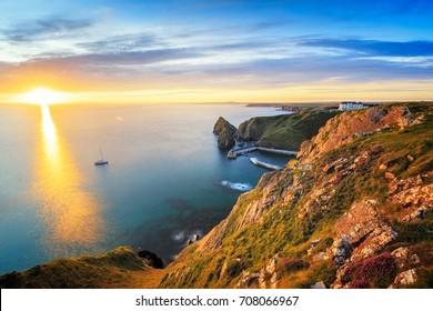 Sunset overlooking Mullion Cove on the Lizard Peninsula Cornwall England UK.
