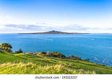 Sunset pacific landscape with a volcano on a horizon. Rangitoto island in Hauraki gulf, view from Devonport, Auckland. New Zealand.