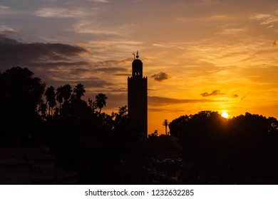 Sunset, palms with Koutoubia Mosque minaret (Djemma el Fna tower) in old medina of Marrakech, Morocco. Touristic  place in Marrakesh used by local people as square or market place.