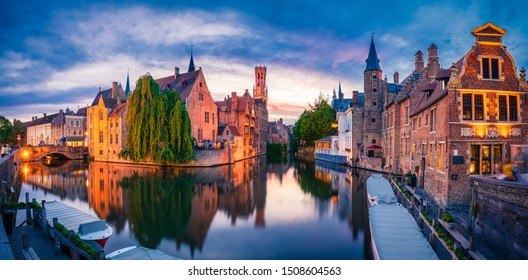 Sunset panorama of center of Brugge, often referred to as The Venice of the North, with famous Rozenhoedkaai illuminated in beautiful twilight, West Flanders province, Belgium