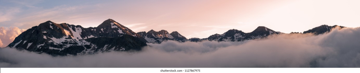 Sunset panorama taken from near the Refuge du Rulhe in the French Pyrenees mountain range. The Pic de Fontargente and Pic de la Coume d'Enfer on the France-Andorra border are visible above the clouds.