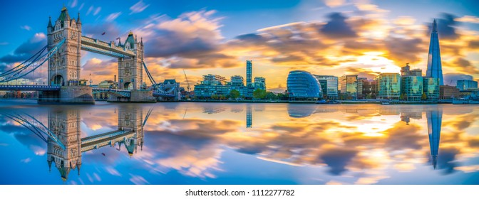 Sunset panorama of Tower Bridge with reflections in London, UK