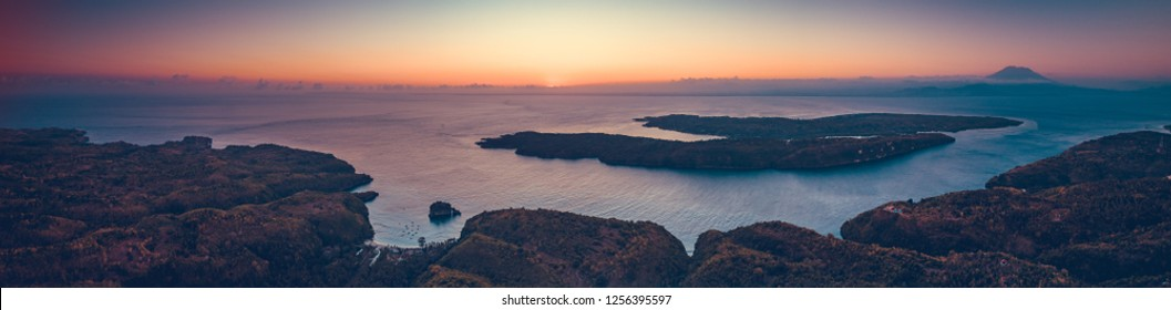 Sunset panoramic overview of Indonesia shoreline and ocean. Aerial drone shot of Asian wild nature. Breathtaking landscape. Sunset over the Indonesian land and calm ocean. Bright colorful sky.
