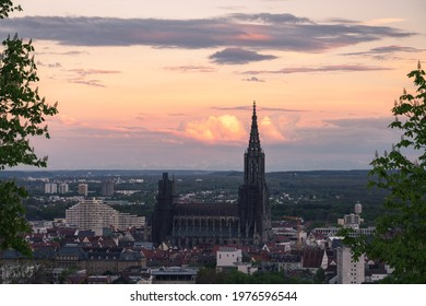 Sunset Panorma Mountain range alps with city ulm and ulmer minster take from a far distance at sunrise sunset dramatic spring sky and blooming tree