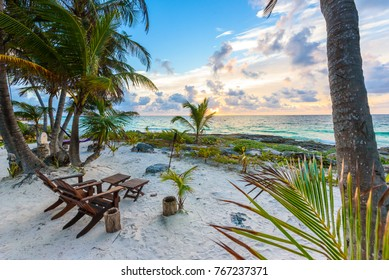 Sunset at paradise beach - Chairs under the palm trees on beach at tropical Resort. Riviera Maya - Caribbean coast at Tulum in Quintana Roo, Mexico