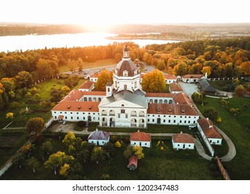 Sunset at the Pazaislis monastery, surrounded by trees colored by autumn colors. Aerial view photographed in Kaunas, Lithuania.