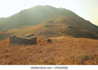 Sunset Peak grassland view with abandoned stone house in winter under the sun light in Hong Kong Lantau Island