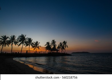 sunset photo  near Tanjung Aru Beach in Sabah, Malaysia with silhouette photo of a building and coconut tree