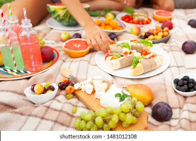 Sunset picnic on grass. Woman mother and kids son and daughter eat fruits and vegetables, cheese and  juice on beige carpet. Nice vocation with family outside. Horizontal.  Only hands and legs.