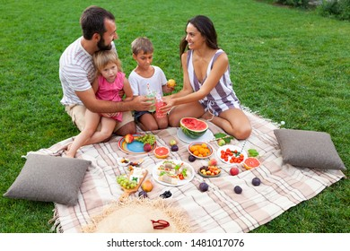 Sunset picnic on grass. Woman mother, man father and kids son and daughter eat fruits and vegetables, cheese and  juice on beige carpet. Nice vocation with family outside. Only hands and legs.