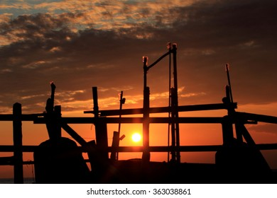 Sunset and the pillars of wood sink.
