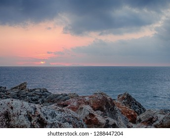 sunset with pink and blue clouds over a calm Mediterranean sea against textured rough coastal rocks in menorca