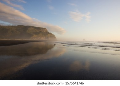 A sunset with pink clouds and blue sky reflected in the low tide water at Karekare Beach in West Auckland, New Zealand. There is black iron sand, golden light, surf, coastal mountains and misty haze.