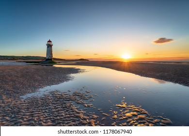 Sunset at the Point of Ayr lighthouse on the beach at Talacre in Flintshire in north Wales