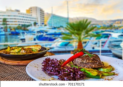 The sunset in port is perfect time to choose the restaurant and enjoy the dinner - grilled beef with chili pepper, lettuce leaves and hot spicy fried potato, Eilat, Israel.