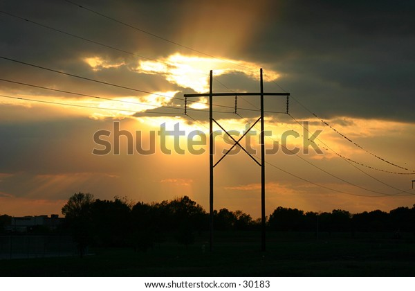 Sunset with power line and sunbeams.