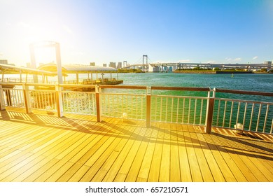 Sunset promenade walkway and jetty where waterbuses and ferry boats arrive at Odaiba Seaside Park in Odaiba island, Tokyo, Japan. Urban cityscape of Rainbow Bridge with Tokyo Skyline on background.