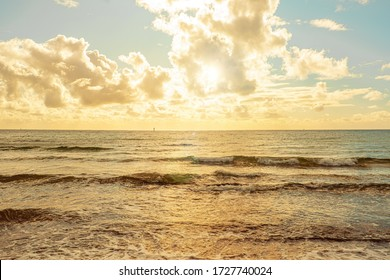 Sunset protruding through clouds over sea waves