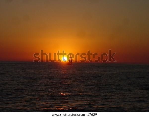 Sunset in Puerto Vallarta Mexico with a sailboat passing through the sun