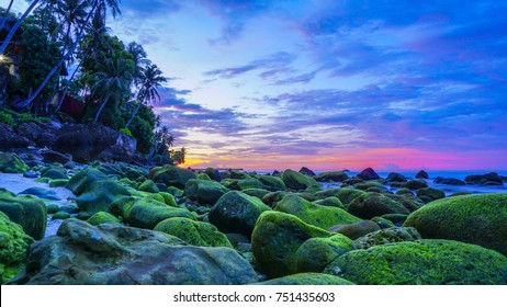 Sunset at Pulau Weh Sabang Acheh Indonesia from low angle with green moss formation on the rocks