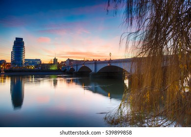 Sunset at Putney Bridge, London with a weeping willow tree in the foreground and reflections in the river.