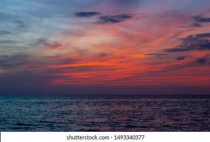 Sunset at Racha (Raja) Noi island near Phuket, Thailand. Twilight and dawn in Andaman sea of Indian ocean. Blue calm ocean and brigh red orange sky and clouds from sailing yacht in cruise.