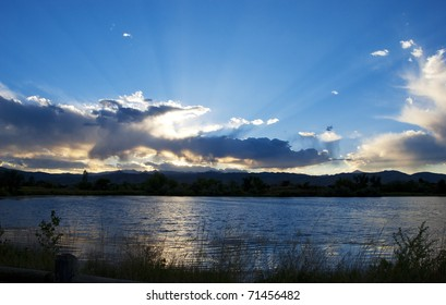 Sunset rays over golden clouds above a dark lake with ripples and grass silhouettes in front.
