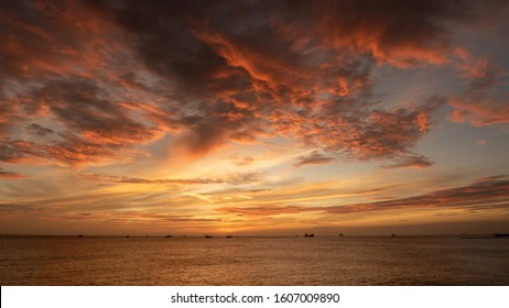 Sunset with red and golden clouds reflecting onto the ocean