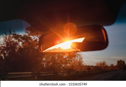 sunset red sunbeams in a salon inside rearview mirror of a car. Close-up, blur.