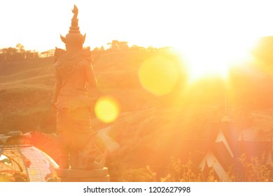 Sunset reflect the orange and yellow flair on the temple and the mountain, Thailand Asia. Close up, macro, soft focus, beautiful in nature outdoor. Magic colorful image