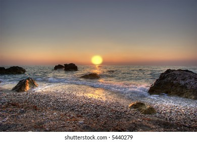 Sunset is reflecting in Ionian sea highlighting wet rocks and pebbles