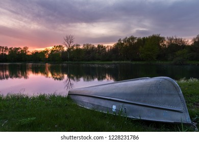 sunset reflecting on a pond with a small paddle boat on the green grassy, shore