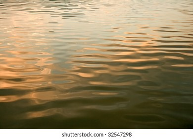 Sunset is reflecting on the surface of a calm lake.