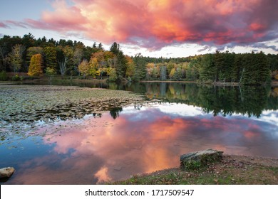 Sunset reflecting in the water of Bass Lake in autumn near Blowing Rock, North Carolina.