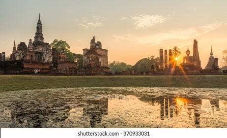 Sunset with a reflection of ancient pagoda and big buddha image at Sukhothai historical park ,UNESCO world heritage site, Sukhothai, Thailand.