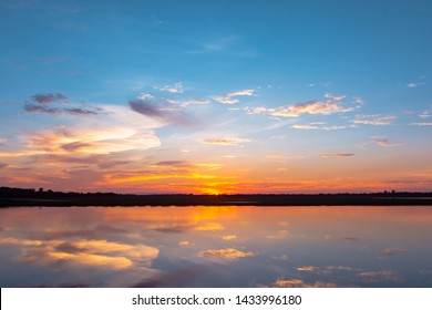 Sunset reflection lagoon. beautiful sunset behind the clouds and blue sky above the over lagoon landscape background. dramatic sky with cloud at sunset