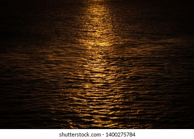 Sunset reflection on the surface of the ocean. Beautiful golden light rays
