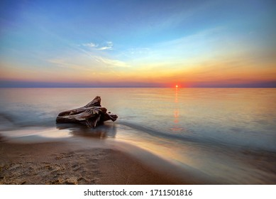 The Sunset Reflection over the Lake with the waves Moving Towards a Piece of Driftwood on the Beach