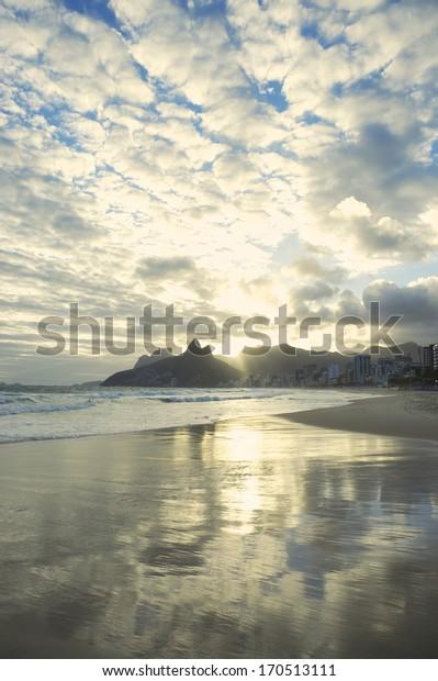 Sunset reflection of Rio de Janeiro Ipanema Beach Brazil with Two Brothers Dois Irmaos Mountain city skyline