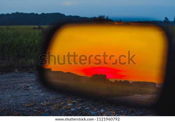 Sunset reflection in the side mirror of the car
